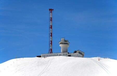 dazzling: Constructions of weather station on snow slope against blue sky in Pyrenees, dazzling colour  Stock Photo