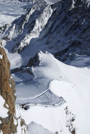 mountainside: White slope with snow paths and skiers between dark mountain range, view from above, Mont Blanc, France