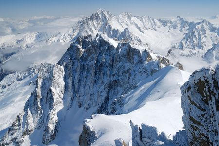mountainside: Sheer cliff in the middle of snow and clouds, white glacial slope, rock with icy pattern in the foreground