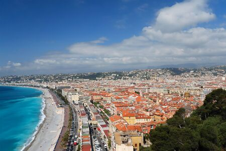 Azure sea bay and blue sky of mediterranean coast, white clouds above old and modern district of city Nice, mountains in the background