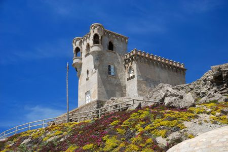 moresque: Moresque building on stony hill moss-grown against blue sky, Castle of Guzman el Bueno Stock Photo