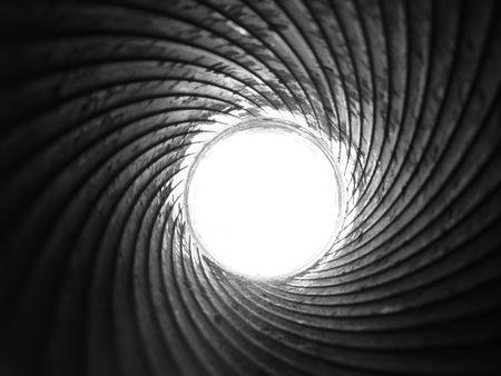 モノクロ画像の内側に大砲のバレルの旋条の光沢のある鋼スパイラルと白いディスク