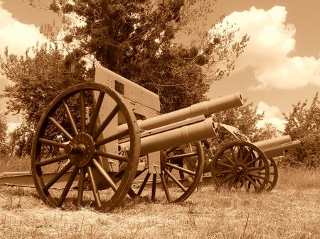 trampled: Obsolete cannons with large wheels on grass trampled down against cloudy sky, field artillery of the first world war, brown monochromatic image Stock Photo