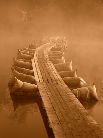 Temporary plank-bridge with many bags floating across the river, silhouettes of persons on far bank in thick fog, brown monochrome image Stock Photo