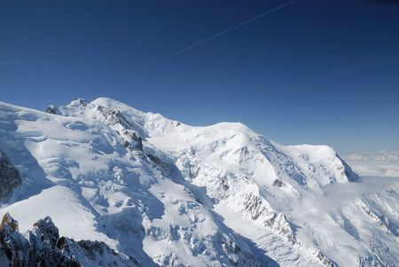 high flown: Clear blue sky above snow-covered peak and glacier flown down, white massive cloud stretching to the skyline Stock Photo