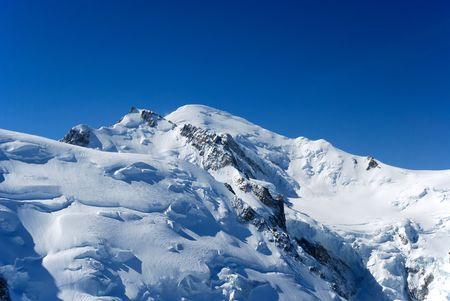 high flown: Clear blue sky above snow-covered peak and glacier flown down