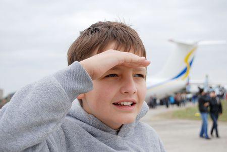 preteen boy: Preteen gar�on jette un regard dans la distance floue contre avion et des personnes, le droit de mettre la main sur le front comme un �cran