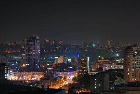 alight: Night cityscape with orange, blue, green light spots in the middle of dark buildings, square and rectangular alight windows, high angle view