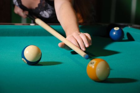 Billiard balls on green felt and cue shot with female hand, blurred silhouette of decollete photo