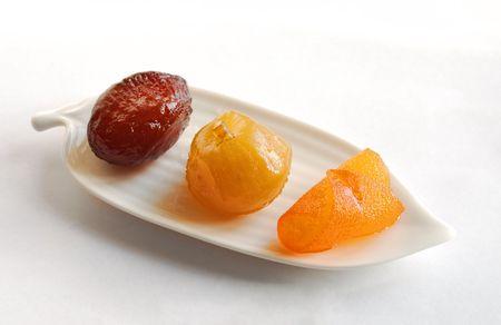 Fico candita, paffuto e fetta d'arancia sul piatto bianco, superficie vetrata di frutta secca