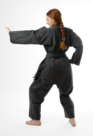 jiu jitsu: Girl in black uniform stands back on half-bent legs, left hand lifted for obstructing, isolated on white