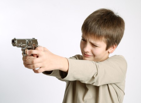Pre-teen boy aiming a silver pistol, concentrated expression of child face