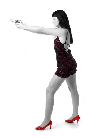 Dark-haired seminude girl aiming a handgun with two hands, black short dress and red shoes, shades of gray