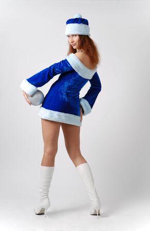 Fairy in blue velvet dress and fur-cap, slender legs in white boots high-heeled, silver christmas ball on left hip Stock Photo - 4041086