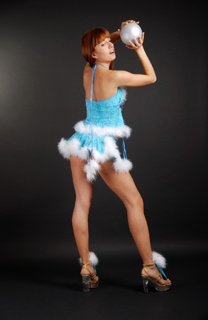 Seminude girl's caught with silver ball, rear view, bright blue fancy dress decorated with white down Stock Photo - 4045443