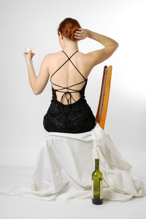 Adult girl sits and holds glass with wine on light background, empty bottle near chair, back , right hand arrange hair photo