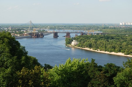 Wide river dividing Kiev into right and left riverside, green islands rank with trees, remote bridges photo