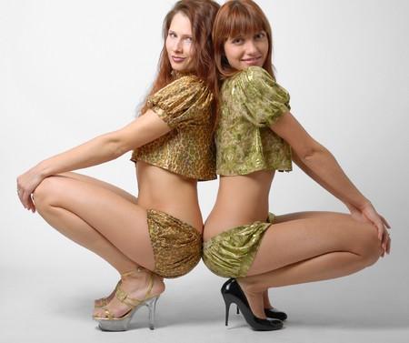 seminude: Seminude giovani donne tacco alto e si siede snuggles insieme, simile a dispetto del nome, buona spiriti Archivio Fotografico