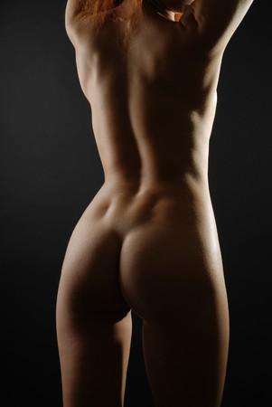 背中、お尻と脚裸の女性のストレッチ n 暗闇の中 写真素材