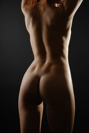 nude woman standing: Back, buttocks and legs of naked woman stretching n the dark