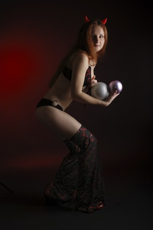 perky: Perky young woman stealing christmas balls in the dark, stage costume of devil