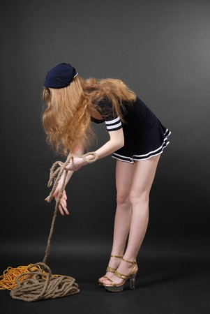 Girl bends down and pulls rope in stage costume of sailor, long hair fallen loose Stok Fotoğraf
