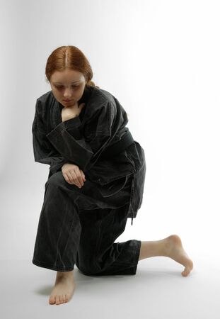 Girl barefooted in dark uniform summons up courage Stock Photo