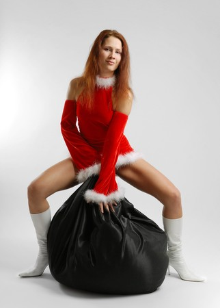 Big sack of gifts between slender legs of young woman in short red dress  Фото со стока