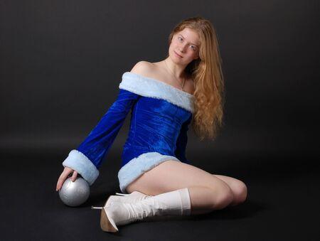 velvet dress: Teenage girl sitting in sexy velvet dress, christmas ball under hand