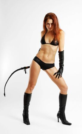 Young woman lashing knout in black lingerie, gloves and boots high-heeled Stock Photo - 4340616