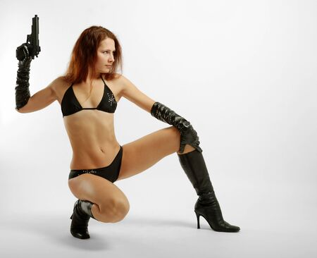 Squatty woman in black lingerie, long gloves and boots with pistol Stock Photo - 4348824