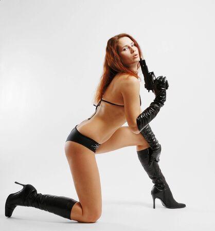 セクシーな女性右膝の上に立つし、銃の煙を吹く