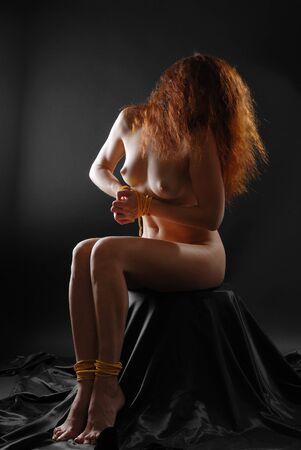 裸の女性と一緒に座ってバインド手と足、低キー 写真素材