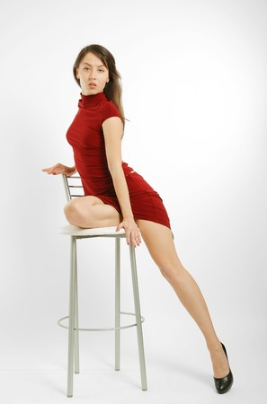 Dark-haired girl in tight short dress sits on high chair and shows slender legs photo