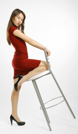 Dark-haired girl in tight short dress plays with stool and shows slender legs photo