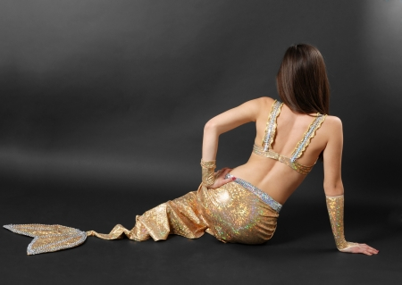 Rear view of woman reclined in stage costume of mermaid on dark background