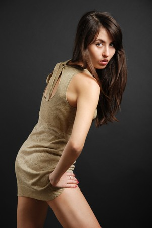 Dark-haired girl bending forward in short dress, provocative look photo