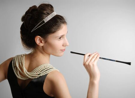 Youth brunette in black dress with pearly necklace and cigar-holder photo