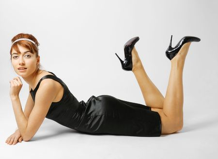 Woman reclining in small black dress, slender legs lifted in heeled shoes photo