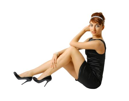 Side view of girl sitting in little black dress, slender legs in heeled shoes photo