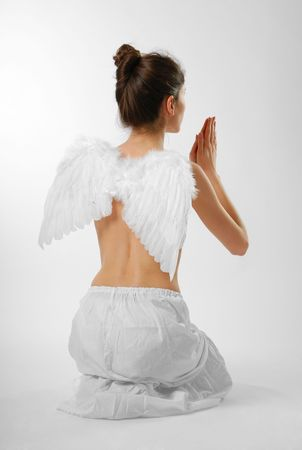 Rear view of girl praying to knees with feathery wings  photo