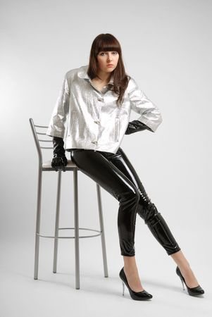 Fashion model sits on edge of high chair in light background. She is wearing varnished trousers, silver jacket and lacquered pumps. Black colour and lustre of pants accentuate slender legs. She is sad and tired.. Stock Photo - 5038080