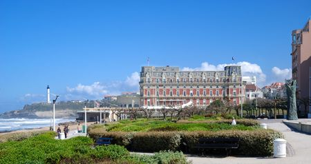 Famous hotel of Biarritz against azure sky. There is square with green park in the foreground. There are cliff with lighthouse and ocean waves surging in the background. Standard-Bild