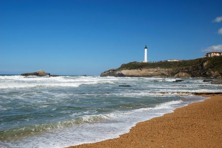 surge: Permanent waves surge in Atlantic coast. The azure sky is over Bay of Biscay. There is cliff with lighthouse in the background.