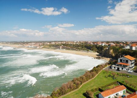 permanent wave: Permanent green waves surge in Atlantic coast. The azure sky with a lot of white clouds is over Bay of Biscay. There are buildings and hotels of Biarritz down coast.