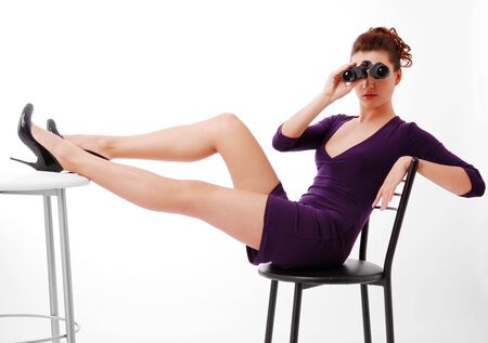 Pretty brunette is sitting on chair isolated on white. Her slender legs are laid on the table. She is watching on binoculars. She is wearing short slinky dress and black pumps with high heels. Stock Photo - 5497352