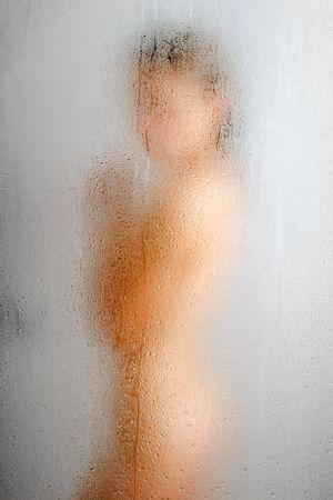 裸の女の子がシャワー、ぼやけ図形の側面にあっています。フォア グラウンドである水で泣くのガラス表面を削除し、ストリームします。焦点はガラスの壁です。 写真素材