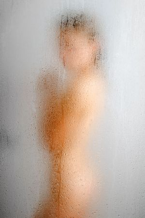 Nude girl is having a shower, side view of blurred shape. In the foreground there is weeping glass surface with water drops and streams. Focus is on the glass wall.  Stock Photo