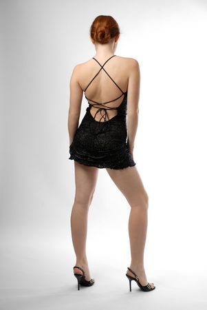 Young woman stands in black dress with naked back on light background. There are a lot of strings on back. Slender legs are high-heeled. Long red hair is arranged nape of the neck.