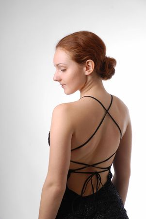 Young woman stands half-turn in black dress with naked back on light background. There are a lot of strings on back. Long red hair is arranged nape of the neck.